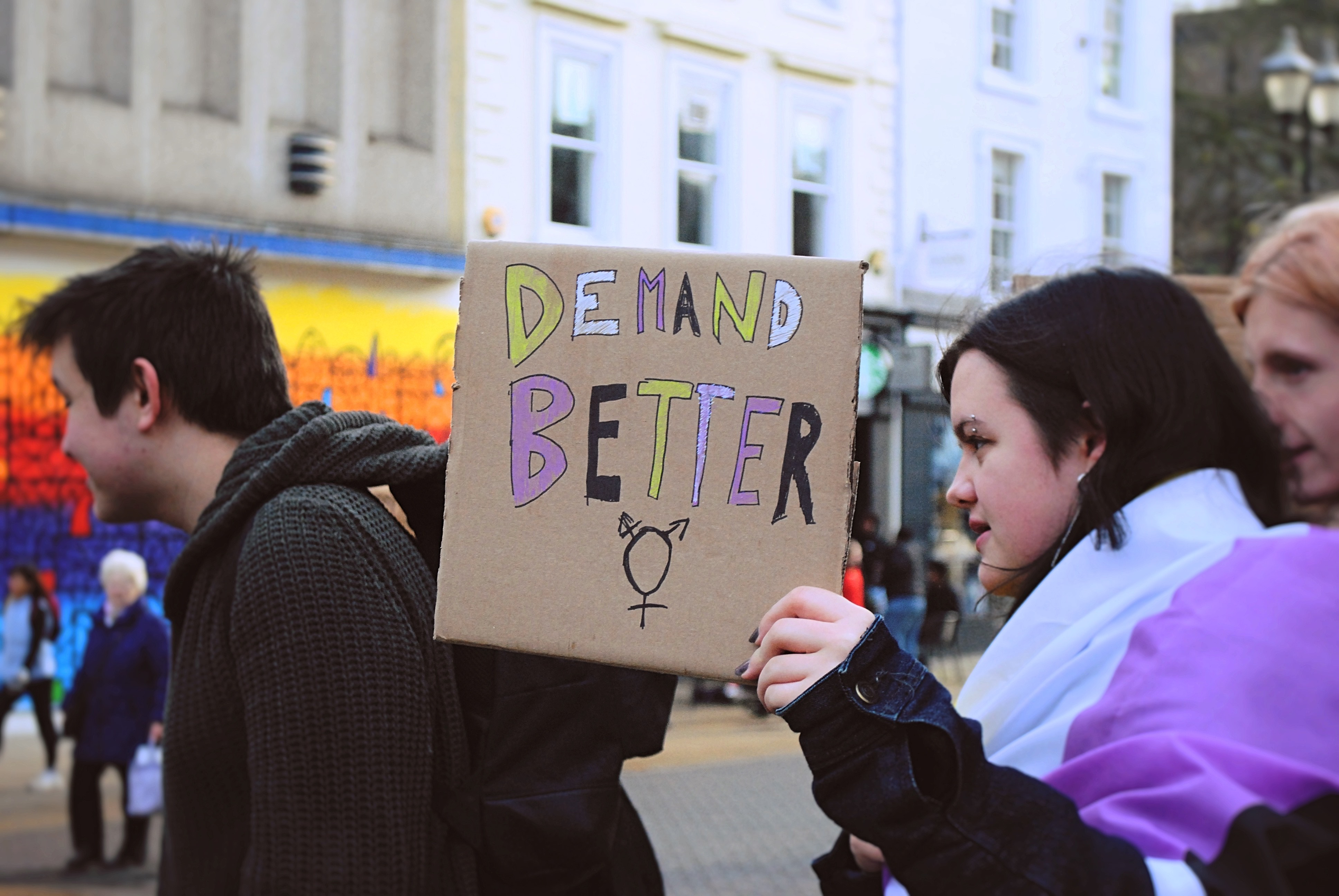 Person holding handmade sign with words 'Demand Better' written on.